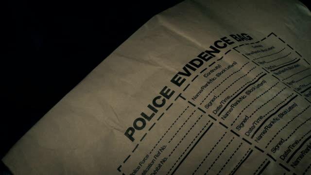 forensics police evidence bag moving shot - schedario documento video stock e b–roll