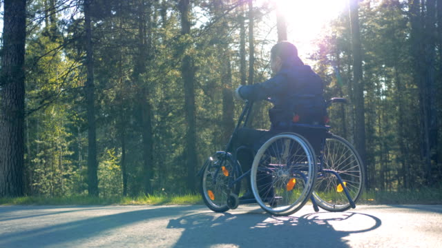 Forest alley with a physically challenged man moving in a training wheelchair video