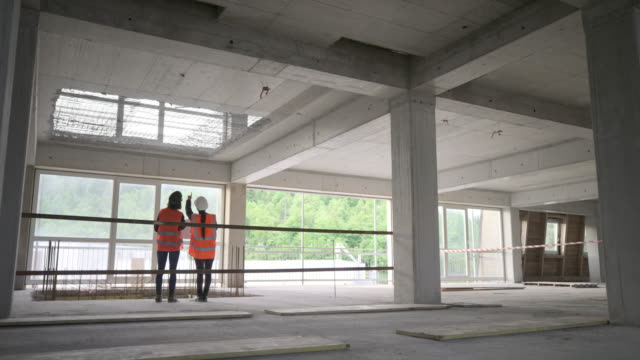 LD Forewoman and female architect standing in the building and talking while checking the detail of the construction