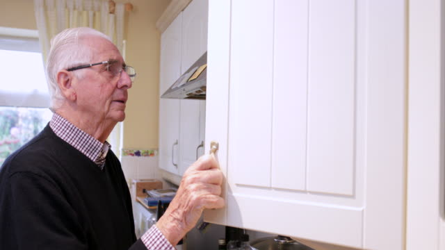Forgetful Senior Man With Dementia Looking In Cupboard At Home