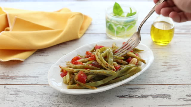 Fork comes to a plate of green beans (zeytinyagli fasulye) video