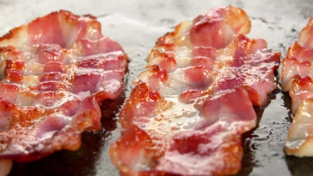 Fork corrects a slice of bacon on the stone grill - video