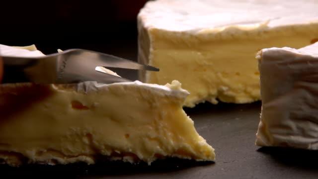 gabel schneidet ein stück köstlichen weichen brie-käse - brie stock-videos und b-roll-filmmaterial