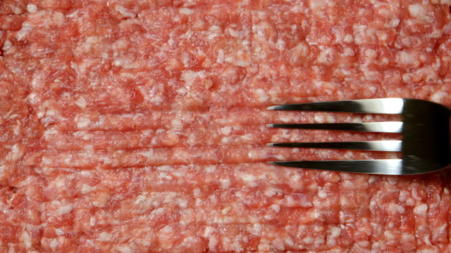 A fork in a cook hand is moving on a fresh forcemeat TOP VIEW: A fork in a cook hand is moving on a fresh forcemeat ground beef stock videos & royalty-free footage