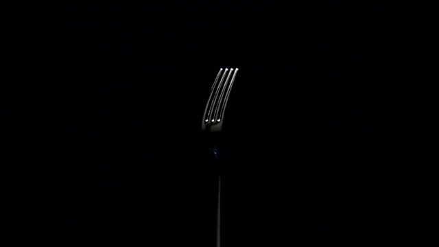 Fork, kitchen cutlery, rotating on black background video