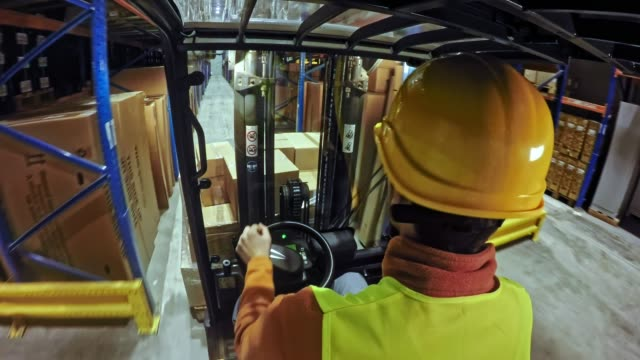 LD Forklift driver driving down the warehouse aisle Wide over the shoulder locked down shot of a forklift driver driving down the aisle in the warehouse. Shot in Slovenia. forklift stock videos & royalty-free footage
