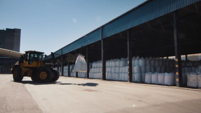 vídeos y material grabado en eventos de stock de cargador de carretilla elevadora es cargando bolsas de carga. - pesado
