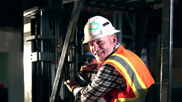 Forklift operator in a warehouse A forklift operator wearing a reflective vest and hardhat, in a warehouse. He is a mature Hispanic man in his 50s. He turns toward the camera and smiles. forklift stock videos & royalty-free footage