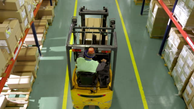 Forklift Operator Working In The Warehouse HD1080p: CRANE shot of a forklift operator transporting the loaded pallet down the pallet racking in the warehouse. forklift stock videos & royalty-free footage