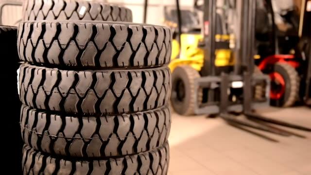 camion con un carrello elevatore di pneumatici operaio cambiando ruote in background - truck tire video stock e b–roll