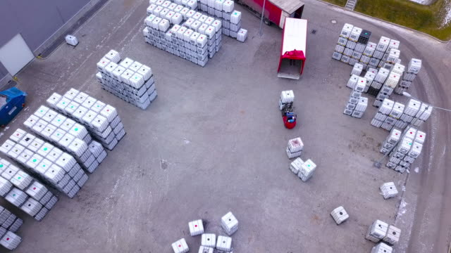 Forklift trucks move between large shelves at outside warehouse and load pallets.Aerial. Drone shot Forklift trucks move between large shelves at outside warehouse and load pallets.Aerial. Drone shot forklift stock videos & royalty-free footage