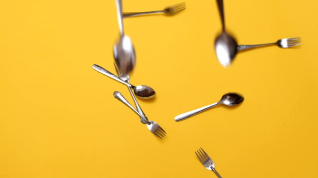 Forks and spoons falling down There are forks and spoons, falling on the yellow background. fork stock videos & royalty-free footage
