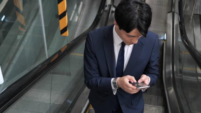 Formal Korean businessman commuting to work and using phone Formal Korean businessman south korea stock videos & royalty-free footage