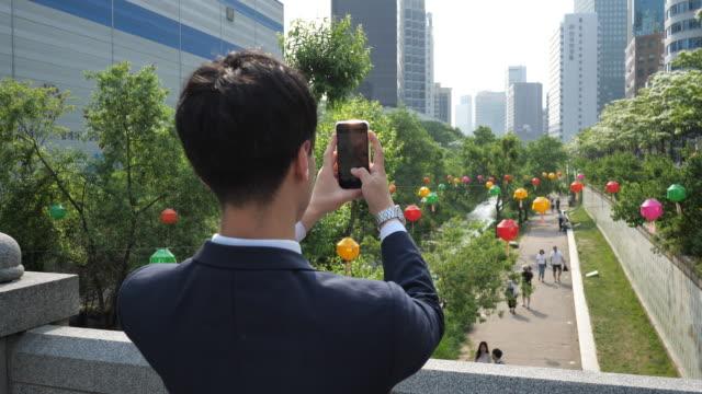 vidéos et rushes de homme d'affaires coréen formel - voyageant à la capitale et appréciant après le travail - photophone
