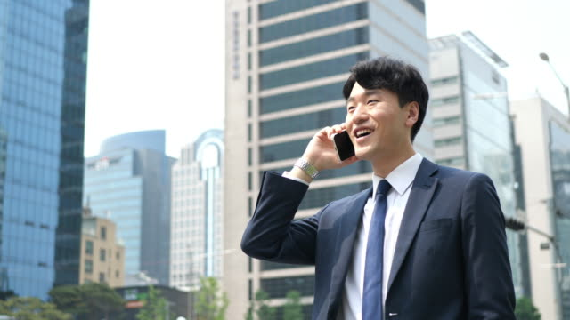 formal korean businessman using phone for communication with business partners - cultura coreana video stock e b–roll