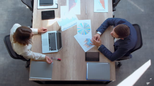 formal meeting in modern office top view business people sitting at the working place. on the desk different documents with tablet and diagrams businesswoman using laptop businessman wearing blue suit. business partners negotiations promotion employment stock videos & royalty-free footage