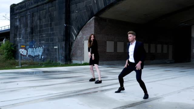 stockvideo's en b-roll-footage met formeel gekleed dansers dansen voor een brug - men blazer