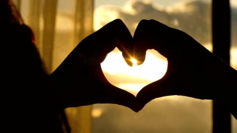 vidéos et rushes de forme de coeur de formation avec le coucher du soleil - doigt humain