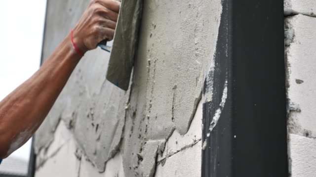 Forming of smooth hard surface on walls Construction worker plastering plasterboard wall with spatula cement stock videos & royalty-free footage