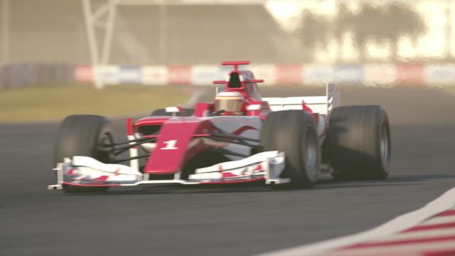 Formula one race car driving through first curve