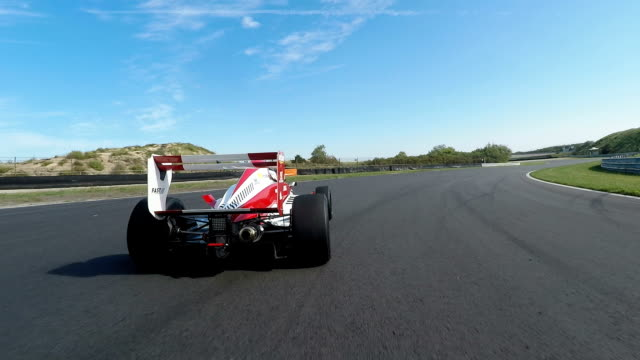 Formula one racing car driving on a racetrack Formula one racing car driving on a racetrack. The camera is behind the racingcar and chases it. chasing stock videos & royalty-free footage