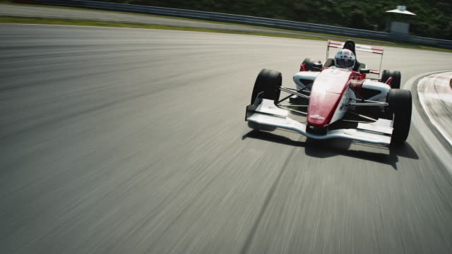 Formular one racing car driving on a racetrack A formula one racing car driving at high speed on a motor racing track. The camera is moving in front of the racecar and is pursuited by it. contest stock videos & royalty-free footage