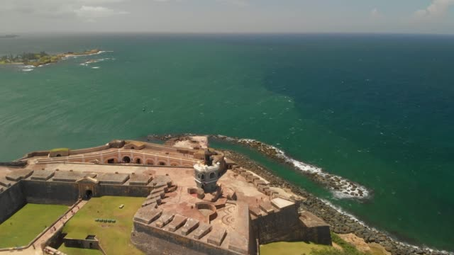Fortress at Old San Juan, Puerto Rico - Castillo San Felipe del Morro Aerial view of the fortress at Old San Juan, Puerto Rico Castillo San Felipe del Morro is a 16th-century citadel located in San Juan, Puerto Rico Puerto Rico is a Caribbean island and unincorporated U.S. territory with a landscape of mountains, waterfalls and the El Yunque tropical rainforest. Its Old San Juan neighborhood features colorful Spanish colonial buildings and El Morro and La Fortaleza, massive, centuries-old fortresses fort stock videos & royalty-free footage
