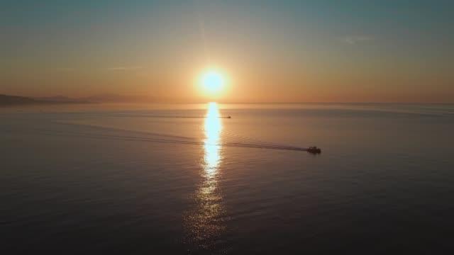 vorwärts luft dolly schuss von sonnenaufgang über dem ozean mit fischerbooten vorbei - horizont über wasser stock-videos und b-roll-filmmaterial