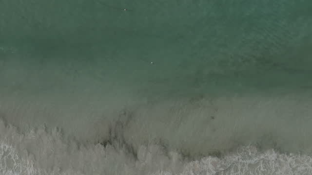 Forward drone shot over breaking waves in the surf on tropical beach with deckchairs video