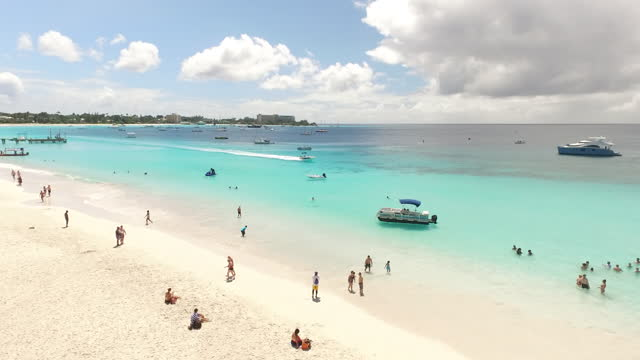 Forward drone shot over busy beach with umbrellas in the Caribbean video
