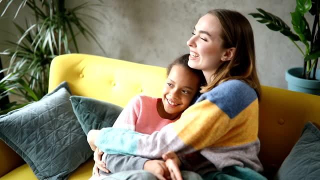 Foster mom and foster daughter embracing and watching TV together