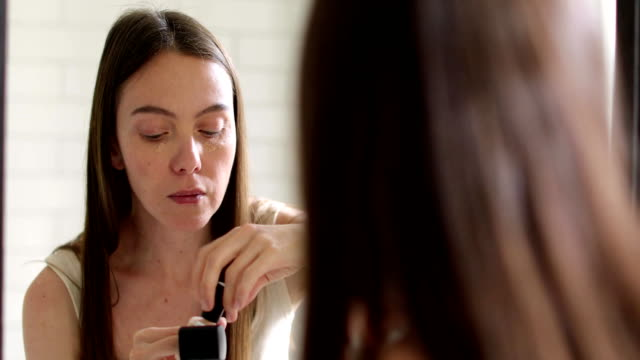 Foundation. Beauty Girl Putting on Makeup Woman puts foundation on her face while looking in reflection in a bathroom mirror foundation make up stock videos & royalty-free footage