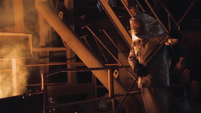 foundry worker with special protective suit. - industria metallurgica video stock e b–roll
