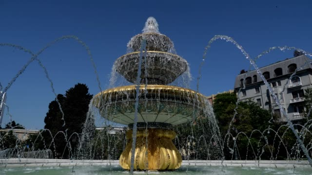 Fountain classical form in three round bowls with cascade jets in city park.