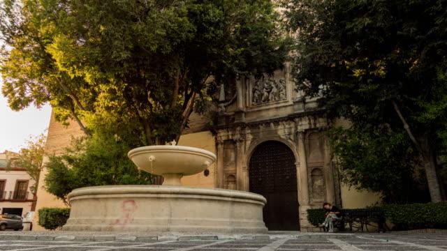 fuente en Sevilla con iglesia timelapse atardecer - vídeo