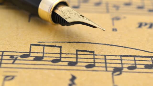 vidéos et rushes de stylo de fontaine sur le projectile de dolly de feuille de musique - compositeur