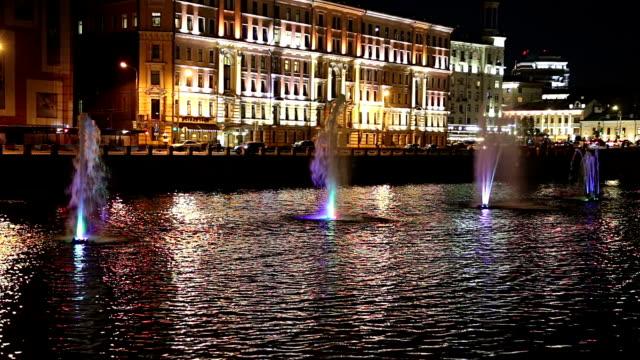 fountains on the drainage channel. bolotnaya embankment and kadashevskaya naberezhnaya (embankment). luzhkov (tretyakov) bridge (at night), moscow city historic center, popular landmark. russia - rzeka moskwa filmów i materiałów b-roll