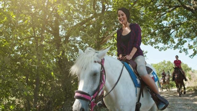 vídeos de stock, filmes e b-roll de quatro pessoas ativas montando cavalos em um ensolarado campo selvagem ao ar livre. viagem italiana de amigos em úmbria.4k câmera lenta - cavalgar