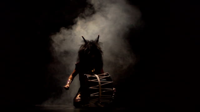 vídeos de stock e filmes b-roll de four artists drummers taiko in a wig with horns and make-up drum on stage against a dark background with smoke. demons from japanese mythology. without sound. - baterista
