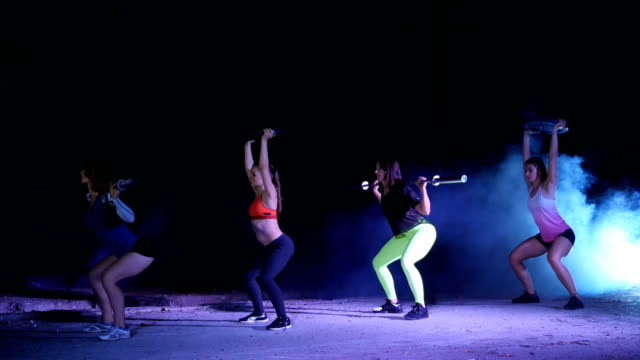 Four athletic sexy women, doing fitness exercises with weightings, At night, in light smoke, fog, in light of a stobascope, in an old abandoned hangar, building Four athletic women, doing fitness exercises with weightings, At night, in light smoke, fog, in light of a stobascope, in an old abandoned hangar, building. human back stock videos & royalty-free footage