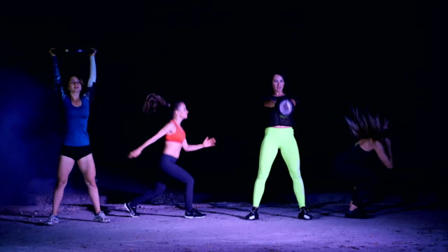 Four athletic women, doing fitness exercises with weightings, At night, in light smoke, fog, in light of a stobascope, in an old abandoned hangar, building Four athletic women, doing fitness exercises with weightings, At night, in light smoke, fog, in light of a stobascope, in an old abandoned hangar, building. human back stock videos & royalty-free footage