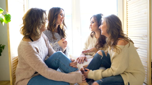 four beautiful girls discuss smile sitting on window. girlfriends having fun and laugh in bedroom - bachelorette party stock videos and b-roll footage