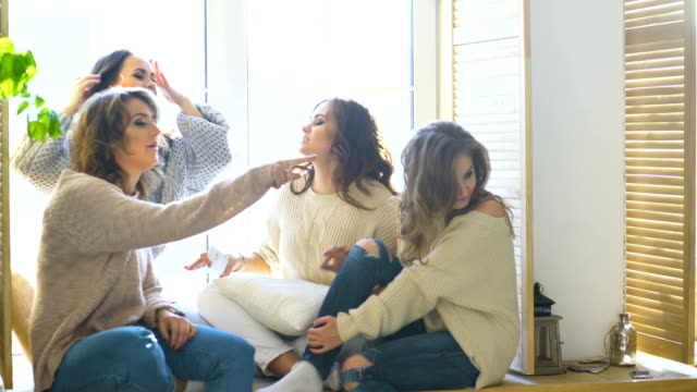 four beautiful girls discuss smile sitting on window. Girlfriends having fun and laugh in bedroom video