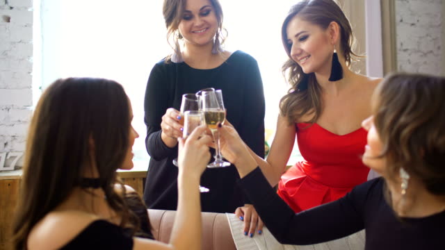 Four beautiful girls drink champagne and cheers. Women having fun laugh in bedroom. video