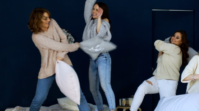 four beautiful girls fight pillows each other on bed slowmotion - bachelorette party stock videos and b-roll footage