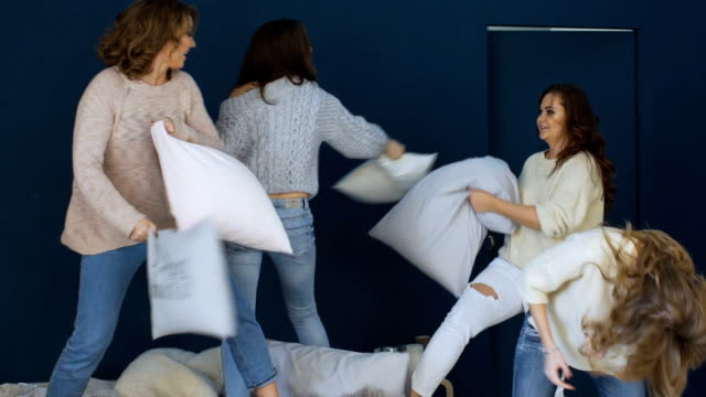 Four beautiful girls fight pillows each other on bed slowmotion video