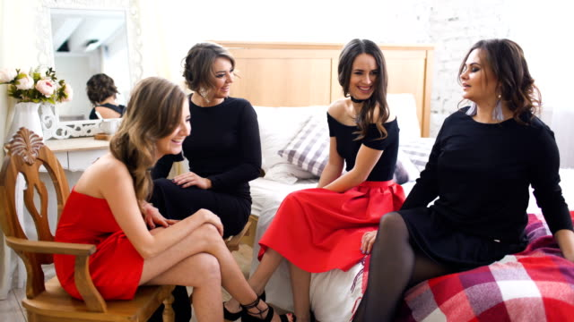 four beautiful girls have gossip talks while sitting on sofa. women having fun laugh in bedroom. - bachelorette party stock videos and b-roll footage