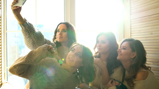 four beautiful girls shoot selfie sitting on window. girlfriends having fun and laugh in bedroom - bachelorette party stock videos and b-roll footage
