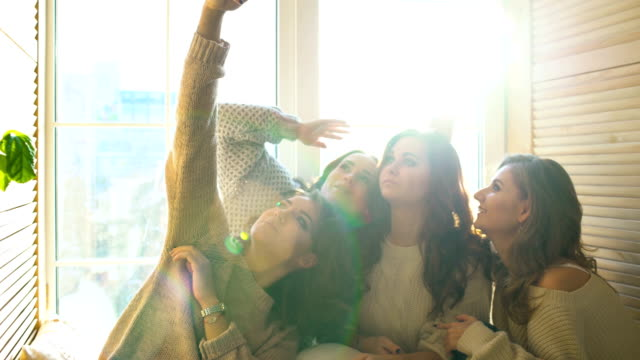 four beautiful girls shoot selfie sitting on window. Girlfriends having fun and laugh in bedroom video