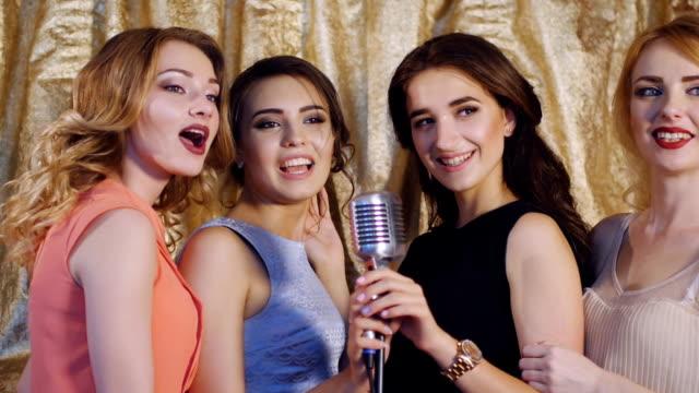 Four beautiful stylish girls singing karaoke at the club video